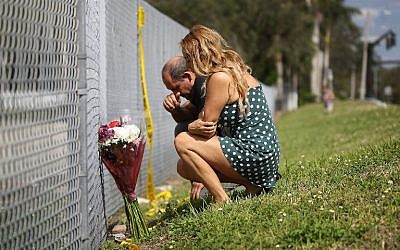 Maria Cristina and Vincent Collazo pray at the fence that runs around Marjory Stoneman Douglas High School on February 18, 2018 in Parkland, Florida. (Joe Raedle/Getty Images)