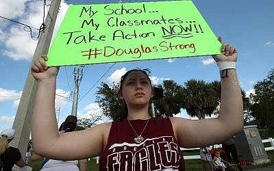 Student Angelia Lazo holds up a sign while standing near the Marjory Stoneman Douglas High School where 17 people were killed on February 14, on February 18, 2018 in Parkland, Florida. (Mark Wilson/Getty Images/AFP)