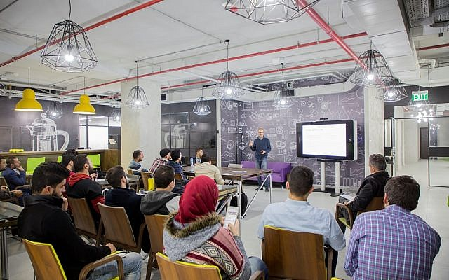 Sari Taha, program manager for Rawabi's collaborative workspace 'Connect,' lectures visitors. (Courtesy)