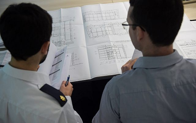 An Israeli Navy officer and German engineer look over plans for a Sa'ar 6 corvette that is under construction for the Israeli Navy in Kiel, Germany, in an undated photograph. (Israel Defense Forces)