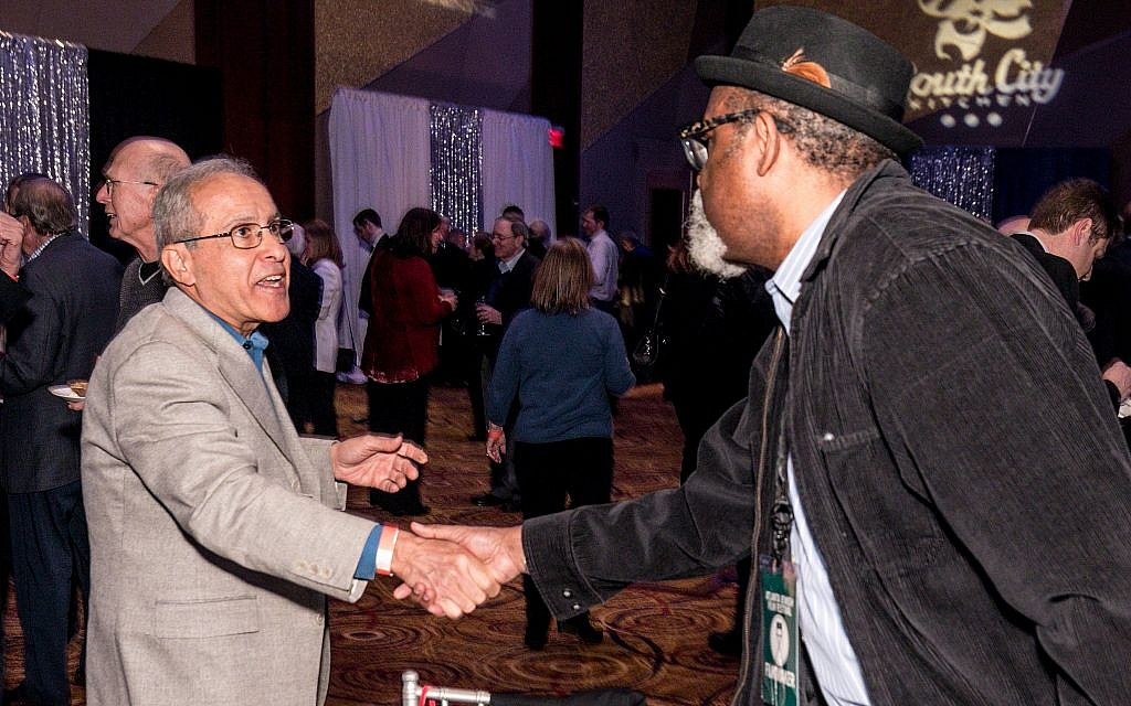 A fan shakes hands with director Sam Pollard, right, at the opening night of the Atlanta Jewish Film Festival, January 24, 2018. (AJFF)
