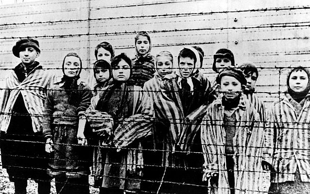 The file picture taken just after the liberation by the Soviet army in January 1945, shows a group of children wearing concentration camp uniforms behind barbed wire fencing in the Oswiecim (Auschwitz) Nazi concentration camp.  (AP Photo)