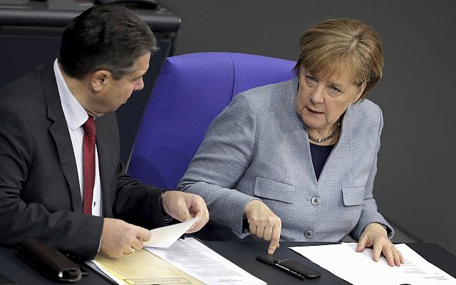 German Chancellor Angela Merkel, right, and German Foreign Minister Sigmar Gabriel, left, talk during a meeting of the German Federal Parliament, Bundestag, at the Reichstag building in Berlin, Germany, February 1, 2018. (AP Photo/Michael Sohn)
