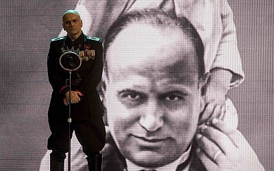 Actor Massimo Popolizio, who plays the part of Benito Mussolini in 'I'm Back,' stands in front of a giant image of the late dictator (Claudio Iannone via AP Photo)