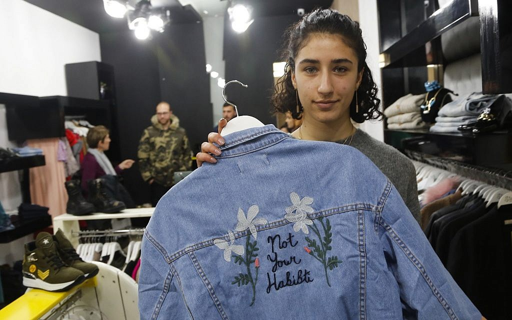 In this Wednesday, Jan. 24, 2018 photo, Palestinian-American Yasmeen Mjalli displays a jacket with the slogan 'Not Your Habibti (darling),' as a ready-made retort for cat calls, in the West Bank city of Ramallah. (AP Photo/Nasser Shiyoukhi)