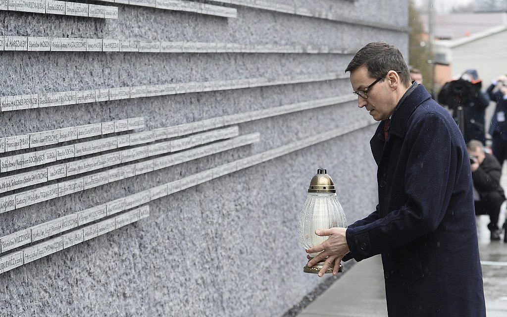 Polish Prime Minister Mateusz Morawiecki places a candle at a memorial wall with names of some of the Poles who saved Jews during the Holocaust, at the Ulma Family Museum of Poles Who Saved Jews during WWII, in Markowa, Poland, Friday, Feb. 2, 2018. (AP/Alik Keplicz)