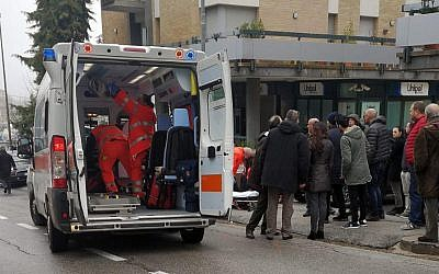 Paramedics attend a wounded man after a shooting broke out in Macerata, Italy, Saturday, Feb. 3, 2018 (Guido Picchio/ANSA via AP)