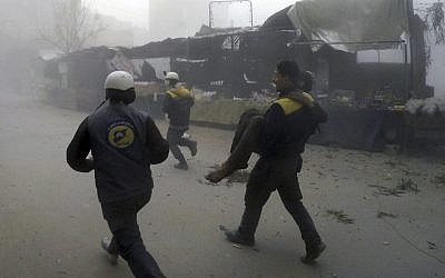 This photo, provided by the Syrian Civil Defense group known as the White Helmets, shows a civil defense worker carrying a wounded man after airstrikes hit a rebel-held suburb near Damascus, Syria, February 5, 2018. (Syrian Civil Defense White Helmets via AP)