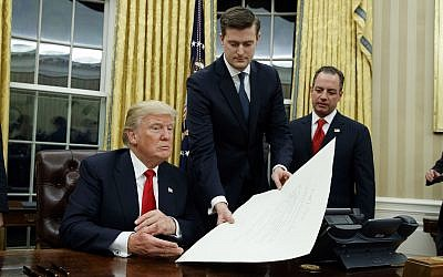 In this January 20, 2017 file photo, White House Staff Secretary Rob Porter, center, hands President Donald Trump a confirmation order for James Mattis as defense secretary, in the Oval Office of the White House in Washington, as White House Chief of Staff Reince Priebus, right, watches. (AP Photo/Evan Vucci)