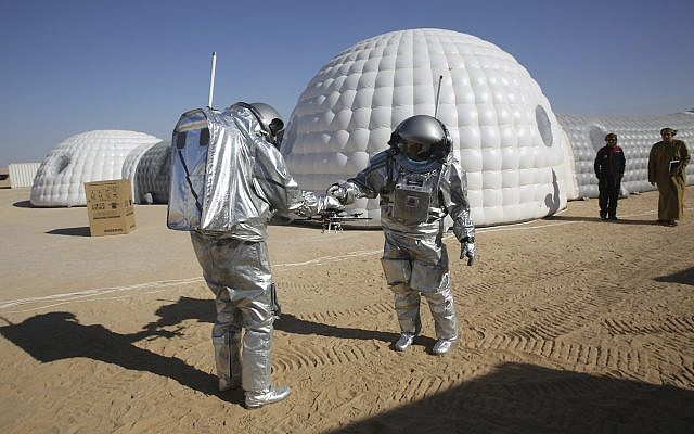 Analog astronaut João Lousada, center, hands his colleague Kartik Kumar a drone while two Omani men watch in front of the Mars simulation base camp in the Dhofar desert of Oman, February 7, 2018. (AP Photo/Sam McNeil)