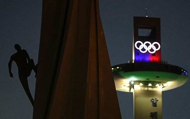 In this Feb. 4, 2018, file photo, a human figure appears to be climbing an Olympic Cauldron at the Pyeongchang Olympic Plaza as preparations continue for the 2018 Winter Olympics in Pyeongchang, South Korea. (AP Photo/Charlie Riedel, File)