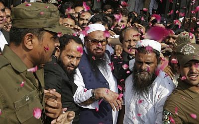 In this photo from October 19, 2017, supporters of Hafiz Saeed, center, shower him with rose petals as he arrives to a court in Lahore, Pakistan. (AP Photo/K.M. Chaudary)