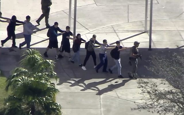 In this frame grab from video provided by WPLG-TV, students from the Marjory Stoneman Douglas High School in Parkland, Fla., evacuate the school following a shooting on February 14, 2018. (WPLG-TV via AP)