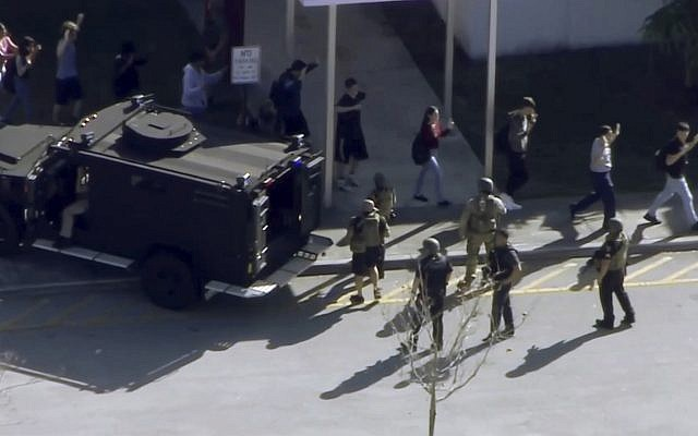 In this frame grab from video provided by WPLG-TV, students from the Marjory Stoneman Douglas High School in Parkland, Florida, evacuate the school following a shooting on February  14, 2018. (WPLG-TV via AP)