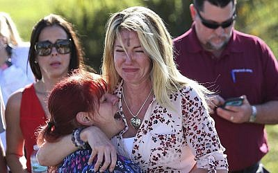 Parents wait for news after reports of a shooting at Marjory Stoneman Douglas High School in Parkland, Florida., on February 14, 2018. (AP Photo/Joel Auerbach)