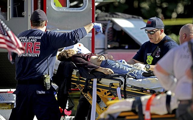 Medical personnel tend to a victim following a shooting at Marjory Stoneman Douglas High School in Parkland, Florida., on Wednesday, Feb. 14, 2018. (John McCall/South Florida Sun-Sentinel via AP)