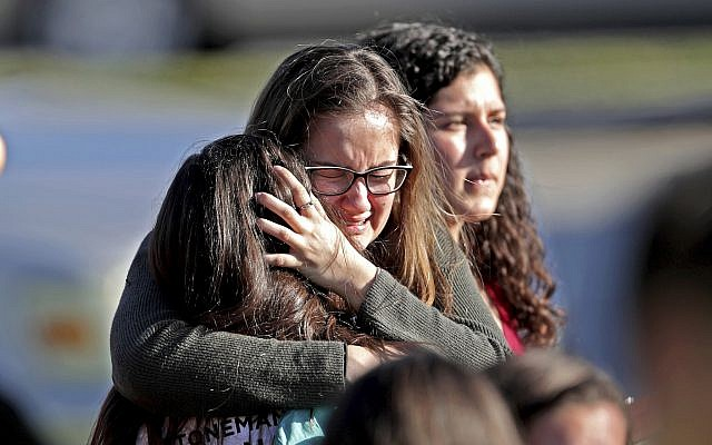 Students released from a lockdown embrace following following a shooting at Marjory Stoneman Douglas High School in Parkland, Florida, February 14, 2018. (John McCall/South Florida Sun-Sentinel via AP)
