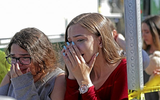 Students released from a lockdown are overcome with emotion following following a shooting at Marjory Stoneman Douglas High School in Parkland, Florida on Feb. 14, 2018. (John McCall/South Florida Sun-Sentinel via AP)