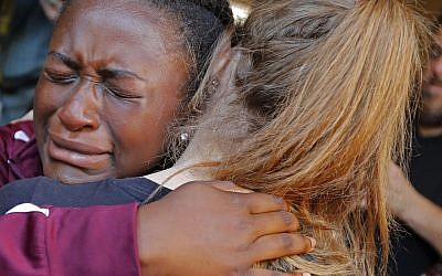 Marla Eveillard, 14, cries as she hugs friends before the start of a vigil at the Parkland Baptist Church, for the victims of Wednesday's shooting at the Marjory Stoneman Douglas High School in Parkland, Florida, February 15, 2018. (AP Photo/Gerald Herbert)