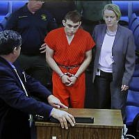 A video monitor shows school shooting suspect Nikolas Cruz (center) with public defender Melisa McNeille (right), making an appearance before Judge Kim Theresa Mollica in the Broward County Court, in Fort Lauderdale, Florida, on Thursday, February 15, 2018. (Susan Stocker/South Florida Sun-Sentinel via AP, Pool)