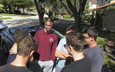 In this February 15, 2018 photo, John Greenberg, center, 17, talks with his friends outside his home in Parkland, Florida. Greenberg and his friends are juniors at Marjory Stoneman Douglas High School, where a former student shot and killed more than a dozen people on February 14. (AP Photo/Jason Dearen)