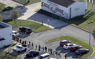 Students are evacuated by police from Marjory Stoneman Douglas High School in Parkland, Florida, after a shooter opened fire on the campus, February 14, 2018. (Mike Stocker/South Florida Sun-Sentinel via AP)