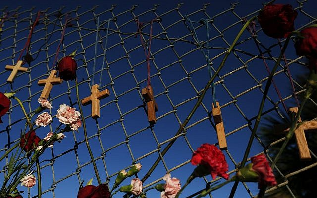 Crosses and flowers hang on a fence near Marjory Stoneman Douglas high school in Parkland, Florida, Saturday, February 16, 2018, in memory of the 17 people killed in a school shooting on Wednesday. (AP Photo/Brynn Anderson)