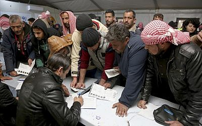 Syrian refugees register their names at an employment office, February 18, 2018, at the Azraq Refugee Camp, 100 kilometers (62 miles) east of Amman, Jordan. (AP Photo/Raad Adayleh)