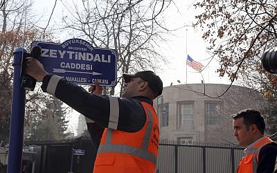 "An Ankara municipality worker fixes the new street sign, ""Olive Branch Street"" in Turkish, named after Turkey's military operation to drive out the Syrian Kurdish militia of an enclave in northwest Syria, in Ankara, Turkey, on February 19, 2018. (AP Photo/Burhan Ozbilici)"