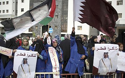 Hospital cleaners hold signs thanking Qatar and wave Qatari and Palestinian flags during a press conference by Matthias Schmale, UNRWA's director in Gaza, and the Qatari envoy, Mohammed Al-Emadi, at the Shifa Hospital in Gaza City, Gaza, on February 19, 2018. (AP Photo/Khalil Hamra)
