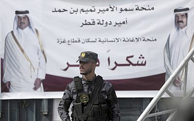 A Palestinian Hamas member stands guard in front of a poster of Qatar's Emir, Sheikh Tamim bin Hamad Al Thani, left, and former Emir of Qatar, Sheikh Hamad bin Khalifa Al Thani, during a press conference with Matthias Schmale, UNRWA's director in Gaza, and the Qatari envoy, Mohammed Al-Emadi, at the Shifa Hospital in Gaza City, Gaza, on February 19, 2018. (AP Photo/ Khalil Hamra)