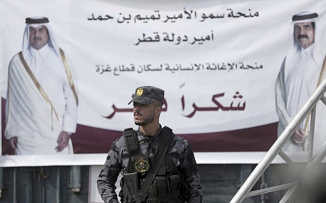 A Palestinian Hamas member stands guard in front of a poster of Qatar's Emir, Sheikh Tamim bin Hamad Al Thani, left, and former Emir of Qatar, Sheikh Hamad bin Khalifa Al Thani, during a press conference with Matthias Schmale, UNRWA's director in Gaza, and the Qatari envoy, Mohammed Al-Emadi, at the Shifa Hospital in Gaza City, Gaza, on February 19, 2018. (AP Photo/Khalil Hamra)