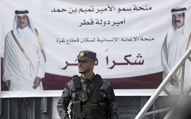 A Palestinian Hamas member stands guard in front of a poster of Qatar's Emir, Sheikh Tamim bin Hamad Al Thani, left, and former Emir of Qatar, Sheikh Hamad bin Khalifa Al Thani, during a press conference with Matthias Schmale, UNRWA's director in Gaza, and the Qatari envoy, Mohammed Al-Emadi, at the Shifa Hospital in Gaza City, Gaza, on February 19, 2018. (AP Photo/Khalil Hamra)