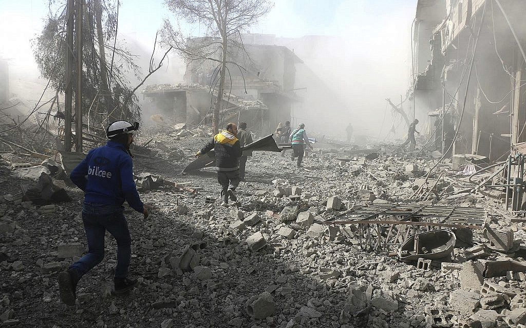 In this photo provided by the Syrian Civil Defense group known as the White Helmets February 20, 2018, shows members of the Syrian Civil Defense running to help survivors from a street that attacked by airstrikes and shelling of the Syrian government forces, in Ghouta. (Syrian Civil Defense White Helmets via AP)