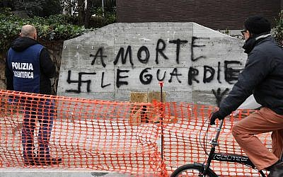 """A forensic police officer looks at graffiti reading in Italian """"Death to the cops"""" on a vandalized monument honoring police killed by Red Brigades terrorists, in Rome, February 21, 2018. (Alessandro Di Meo/ANSA via AP)"""