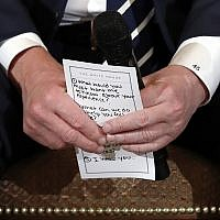 US President Donald Trump holds notes during a listening session with high school students and teachers in the State Dining Room of the White House in Washington February 21, 2018. (AP Photo/Carolyn Kaster)