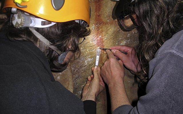 In this undated image provided by João Zilhão in February 2018, Dirk Hoffmann and Alistair Pike take a sample from a calcite crust on top of a red ladder-shaped cave painting in La Pasiega in Puente Viesgo, Spain. (João Zilhão via AP)