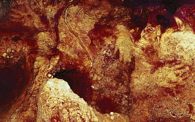 This color enhanced image provided by Hipolito Collado Giraldo in February 2018 shows three hand stencils in the Maltravieso Cave in Cáceres, Spain. (Hipolito Collado Giraldo via AP)