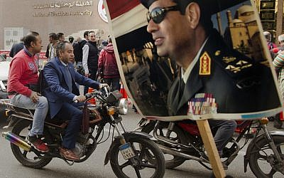 In this January 29, 2018 file photo, a supporter holds a poster showing Egyptian President Abdel-Fattah el-Sissi in front of the National Elections Authority in Cairo, Egypt. (AP Photo/Amr Nabil, File)