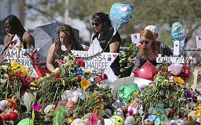 Mourners bring flowers as they pay tribute at a memorial for the victims of the shooting at Marjory Stoneman Douglas High School on Sunday, Feb. 25, 2018, in Parkland, Florida. (David Santiago/Miami Herald via AP)