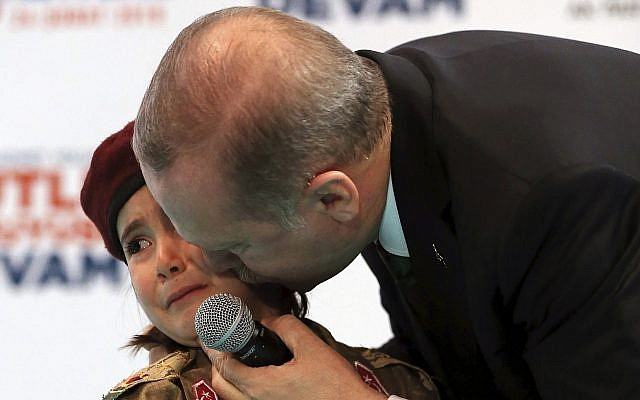 In this photo from February 24, 2018, Turkish President Recep Tayyip Erdogan kisses Amine Tiras, a young girl in military uniform as he speaks to his ruling party members, in Kahramanmaras, Turkey. (Murat Cetinmuhurdar/Pool Photo via AP, File)