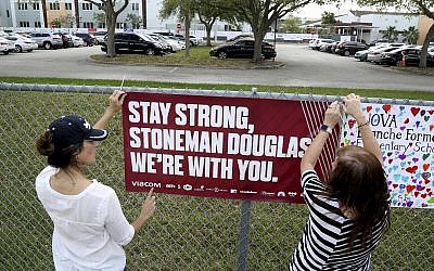 Volunteers hang banners around the perimeter of Marjory Stoneman High School in Parkland, Florida, to welcome back students returning to school Wednesday, February 28, 2018, two weeks after the mass shooting that killed 17 students and staff. (Susan Stocker/South Florida Sun-Sentinel via AP)