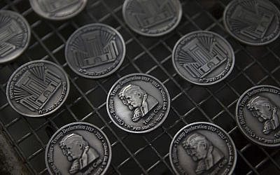 Coins bearing the images of US President Donald Trump and King Cyrus, to honor Trump's recognition of Jerusalem as Israel's capital, are laid out at a private minting facility in Tel Aviv on February 28, 2018. (AP Photo/Sebastian Scheiner)
