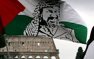 A demonstrator waves a Palestinian flag portraying Yasser Arafat during a demonstration in front of Rome's Colosseum Saturday, Oct. 30, 2004. (AP/Alessandra Tarantino)