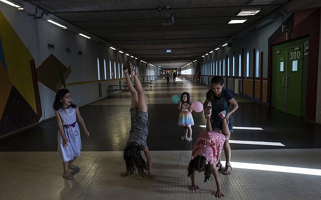 In this July 19, 2017, photo, Syrian refugee girls play in a corridor at the former prison of Bijlmerbajes in Amsterdam, Netherlands. (AP Photo/Muhammed Muheisen)
