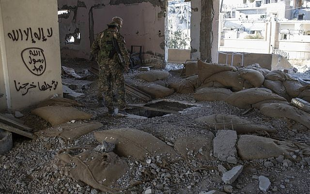 Members of the US-backed Syrian Democratic Forces (SDF) check for bombs at the stadium that was the site of Islamic State fighters' last stand in the city of Raqqa, Syria, Wednesday, October 18, 2017. (AP/Asmaa Waguih)