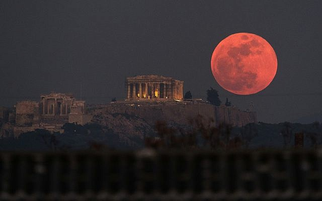 A super blue blood moon rises behind the 2,500-year-old Parthenon temple on the Acropolis of Athens, Greece, on Wednesday, Jan. 31, 2018 (AP Photo/Petros Giannakouris)