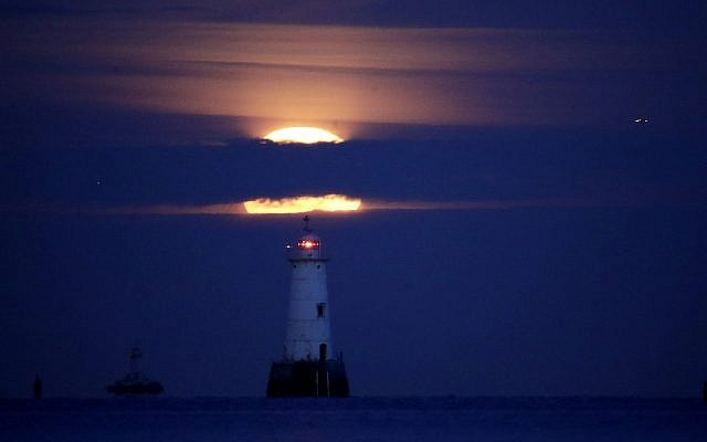 A supermoon rises over the Great Bends Lighthouse on the Raritan Bay, Wednesday, Jan. 31, 2018, in South Amboy, N.J. The super moon is the final of three consecutive supermoons. Earlier in the day, the supermoon phenomenon also experience lunar eclipse as it set over the horizon, but only a partial eclipse was visible in the East Coast. (AP Photo/Julio Cortez)