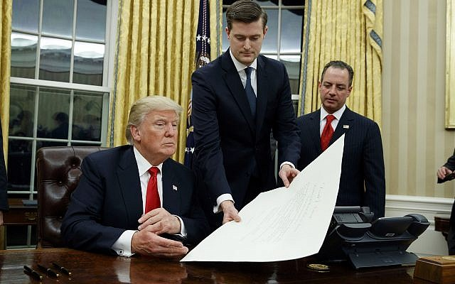 FILE - In this Jan. 20, 2017 file photo, White House Staff Secretary Rob Porter, center, hands President Donald Trump a confirmation order for James Mattis as defense secretary, in the Oval Office of the White House in Washington, as White House Chief of Staff Reince Priebus, right, watches. AP Photo/Evan Vucci)