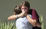 Students grieve outside Pines Trail Center where counselors are present, after Wednesday's mass shooting at Marjory Stoneman Douglas High School in Parkland, Fla., Thursday, February 15, 2018. (AP/Joel Auerbach)